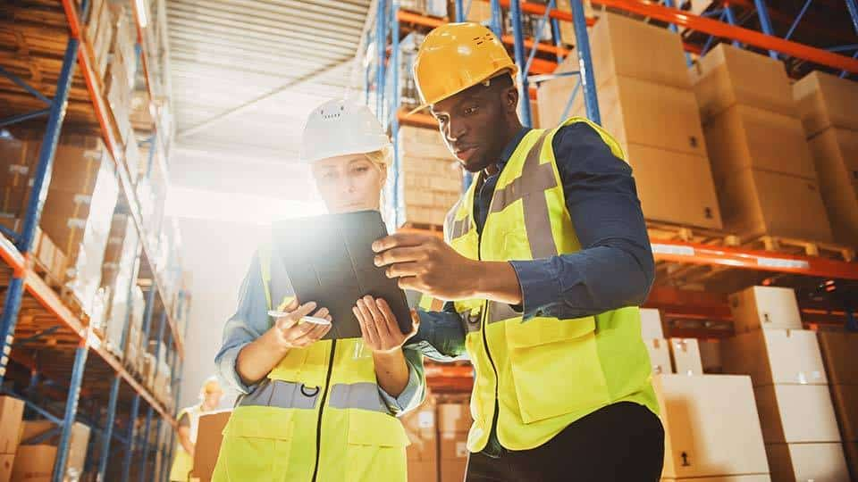 Coworkers in personal protection equipment looking at tablet in warehouse
